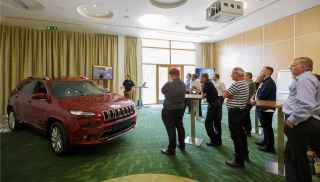 Group looking at a red Jeep car