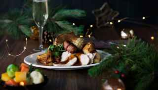 Christmas dinnner on a plate with a glass of prosecco