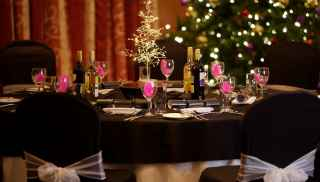Table decorated for a Christmas party with a Christmas tree twinking in the background