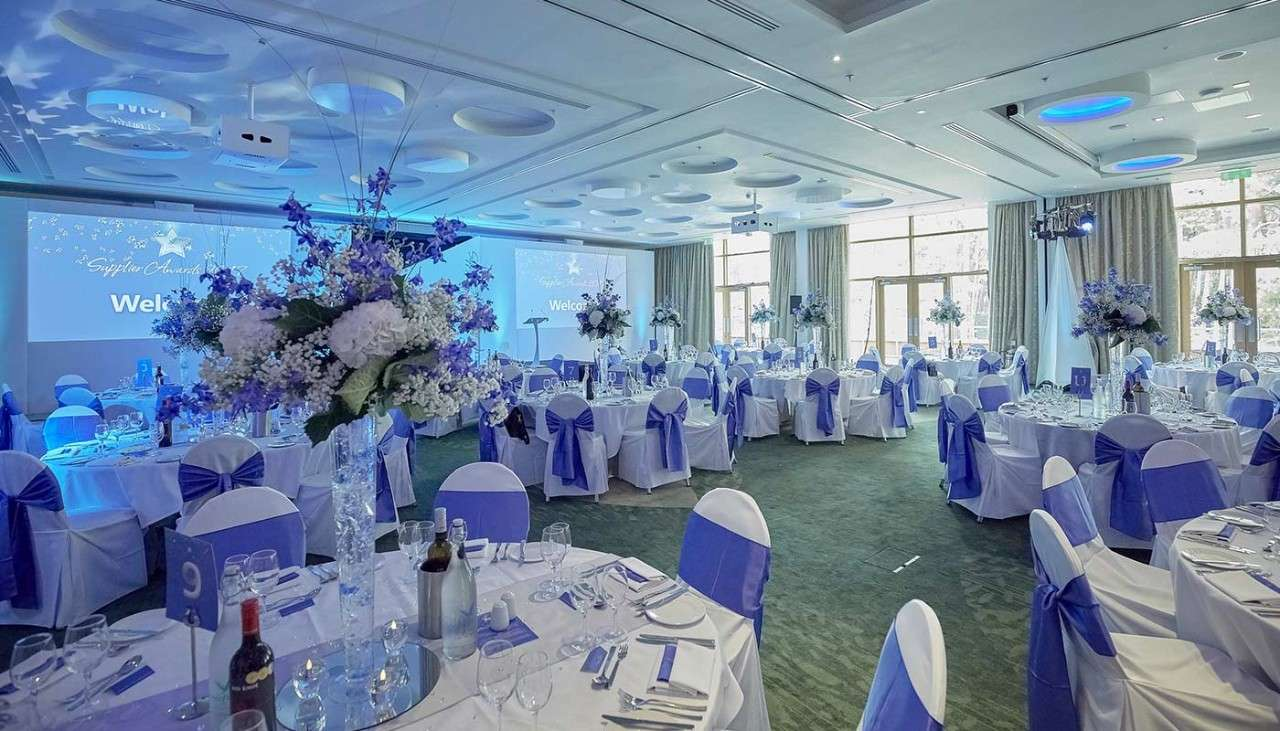 Room decorated with a white and purple theme for an event, with round tables and large flower bouquets as center pieces