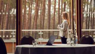 Woman enjoying a cup of tea on a meeting room balcony, taking in the view of the forest