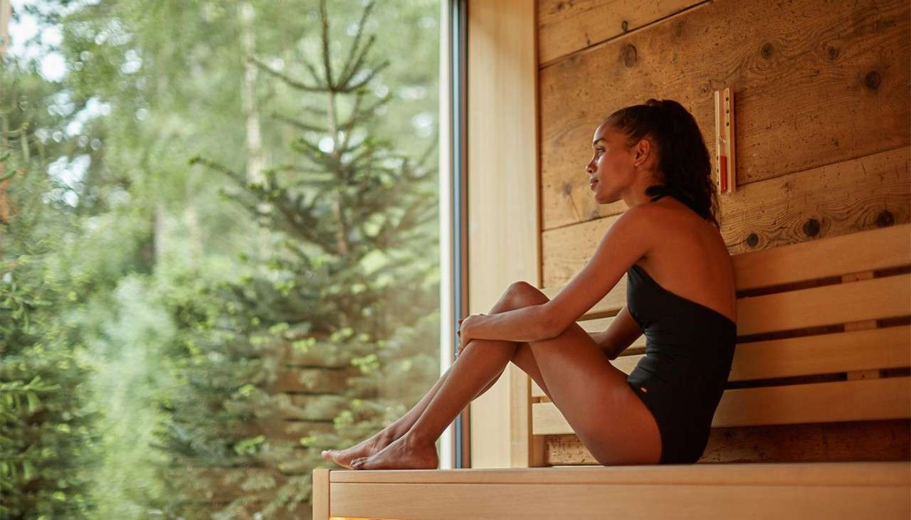 Woman in a sauna looking out to the forest