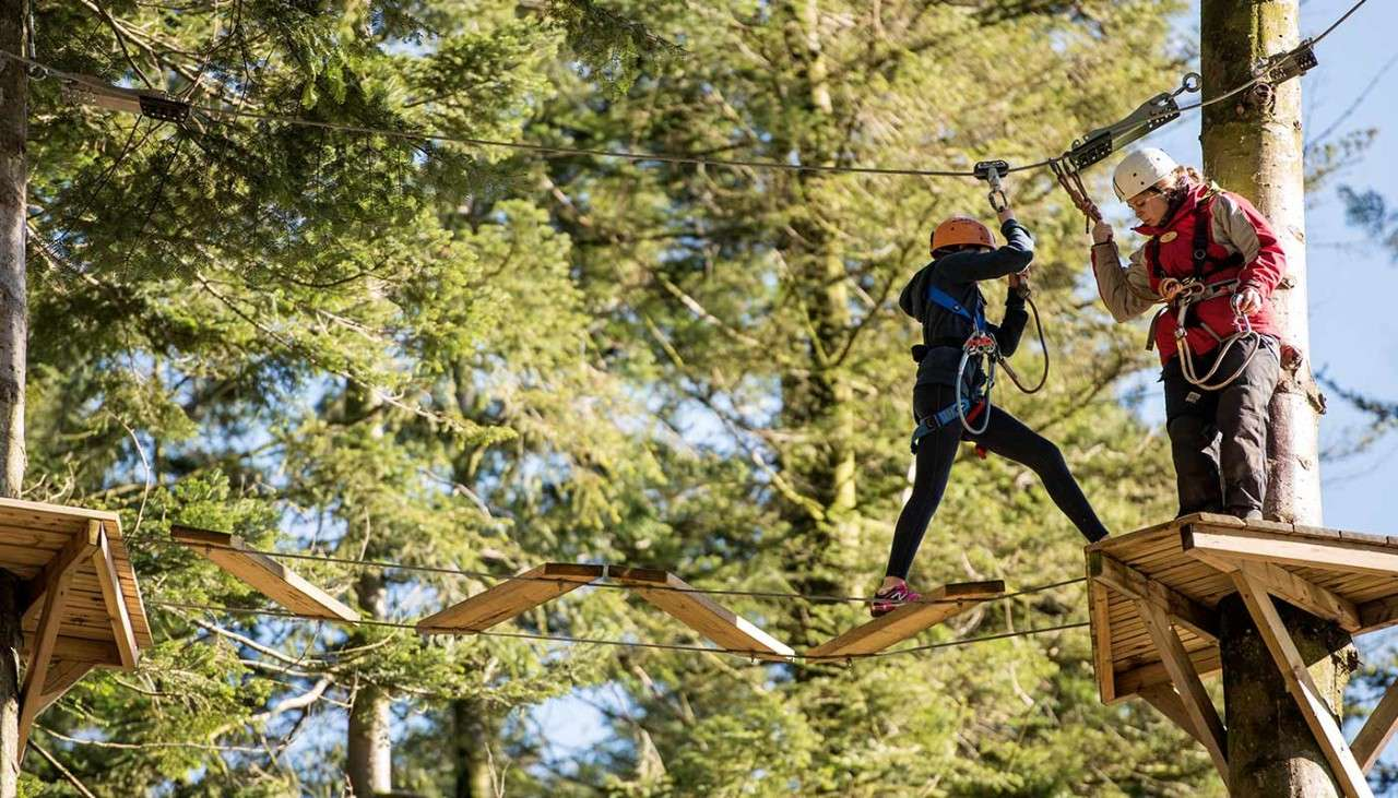 Woman going across obstacles in the treetops